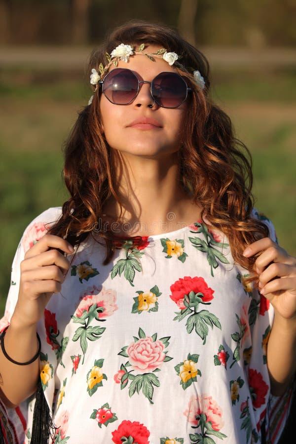 O retrato de uma menina bonito da hippie nos óculos de sol guarda pontas do cabelo das mãos fora fotografia de stock royalty free