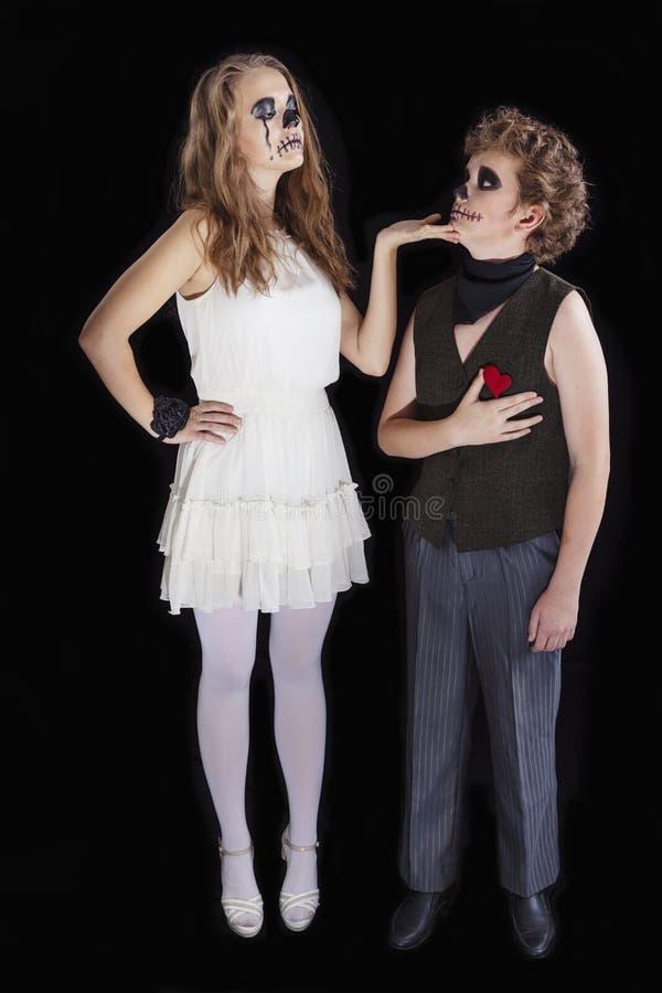 O retrato de uma menina e de um menino vestiu-se para a celebração do Dia das Bruxas foto de stock