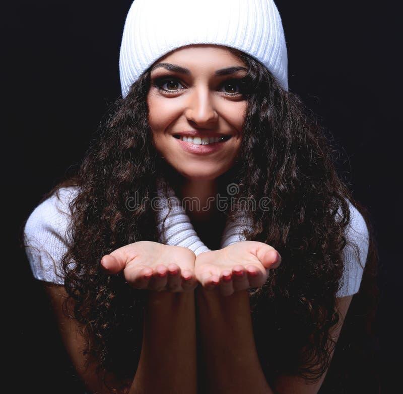 O retrato de uma menina em um chapéu feito malha branco envia um beijo foto de stock