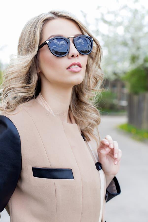 O retrato de uma menina engraçada 'sexy' bonito bonita nos óculos de sol com um sorriso bonito em um revestimento anda em ruas da foto de stock