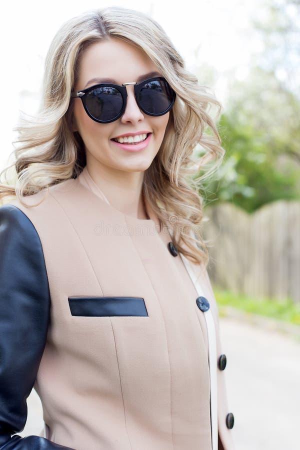 O retrato de uma menina engraçada 'sexy' bonito bonita nos óculos de sol com um sorriso bonito em um revestimento anda em ruas da imagens de stock