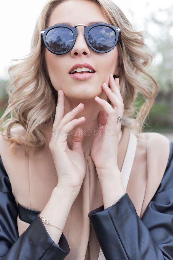 O retrato de uma menina engraçada 'sexy' bonito bonita nos óculos de sol com um sorriso bonito em um revestimento anda em ruas da fotos de stock