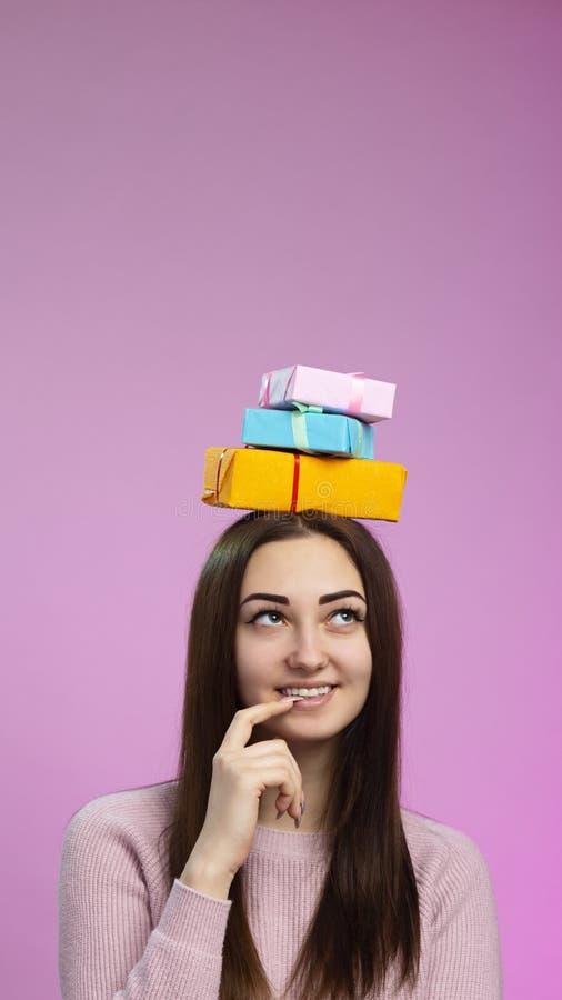 O retrato de uma menina feliz uma pilha das caixas de presente em sua cabeça, jovem mulher de sorriso imagina com um dedo perto d foto de stock