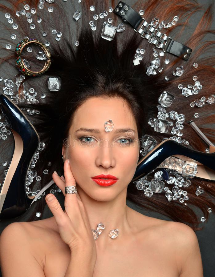 O retrato de uma menina moreno luxuoso encontra-se em um placer da joia dos diamantes, acess?rios luxuosos imagem de stock royalty free