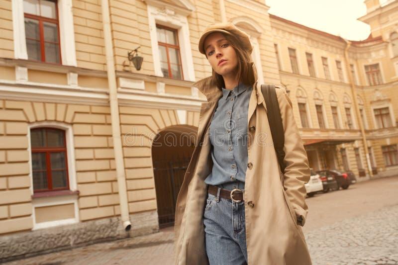 O retrato de uma menina nova bonita do moderno anda através das ruas o divertimento e o sorriso velhos da cidade fotografia de stock royalty free