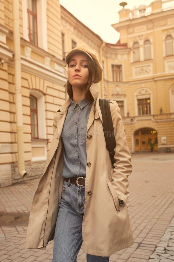 O retrato de uma menina nova bonita do moderno anda através das ruas o divertimento e o sorriso velhos da cidade imagem de stock