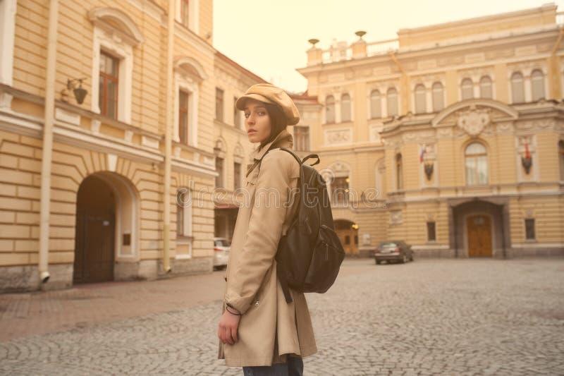 O retrato de uma menina nova bonita do moderno anda através das ruas o divertimento e o sorriso velhos da cidade fotografia de stock