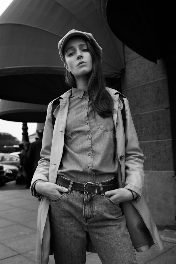 O retrato de uma menina nova bonita do moderno anda através das ruas o divertimento e o sorriso velhos da cidade imagens de stock royalty free