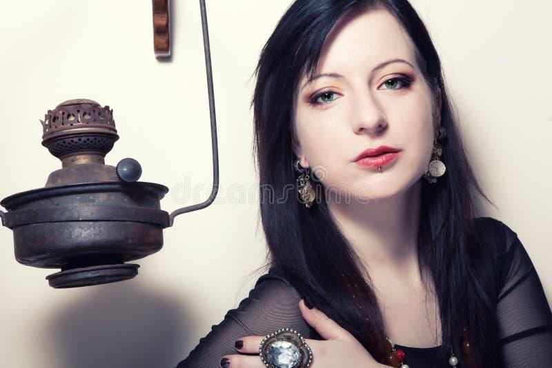 O retrato de uma menina polonesa bonita nova com olhos verdes vestiu-se em um espartilho na perspectiva de um moedor de café do v imagens de stock royalty free