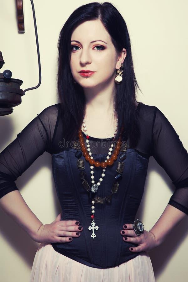 O retrato de uma menina polonesa bonita nova com olhos verdes vestiu-se em um espartilho na perspectiva de um moedor de café do v imagem de stock royalty free