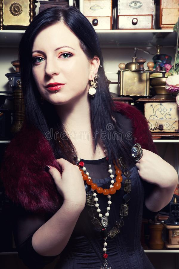 O retrato de uma menina polonesa bonita nova com olhos verdes vestiu-se em um espartilho na perspectiva de um moedor de café do v fotografia de stock