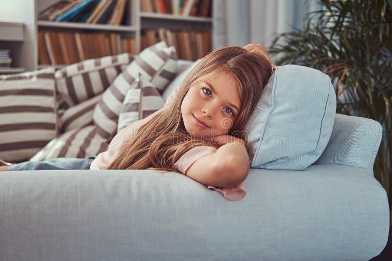 O retrato de uma menina de sorriso com cabelo marrom longo e a perfuração olham, encontrando-se em um sofá em casa fotos de stock royalty free
