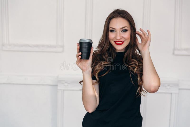 O retrato de uma moça bonita brilhante, abertamente e amplamente sorrindo, guarda sua tisana deliciosa em suas mãos imagem de stock royalty free
