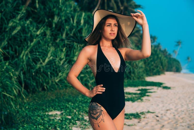 O retrato de uma moça bonita em um roupa de banho clássico está estando na costa, honrando na perspectiva de fotografia de stock royalty free