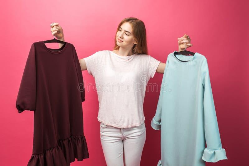 O retrato de uma moça bonita escolhe um vestido, não pode ser determinado, no fundo cor-de-rosa, anunciando fotos de stock royalty free