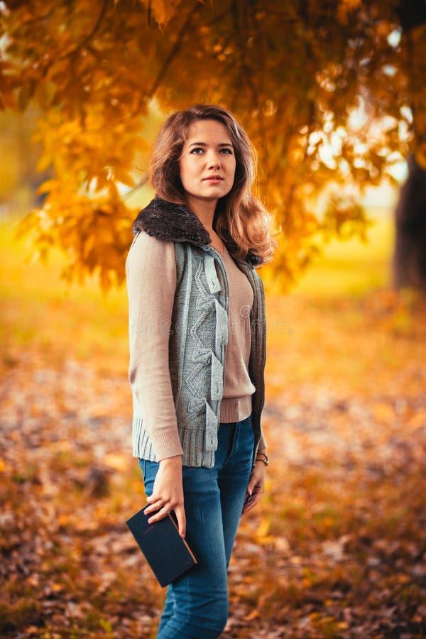 O retrato de uma moça na veste da pele e o livro de leitura no outono do fundo estacionam imagem de stock