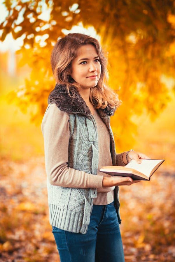 O retrato de uma moça na veste da pele e o livro de leitura no outono do fundo estacionam fotografia de stock