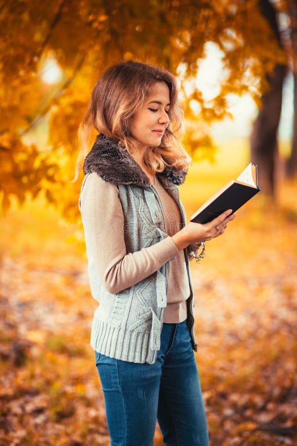 O retrato de uma moça na veste da pele e o livro de leitura no outono do fundo estacionam foto de stock royalty free