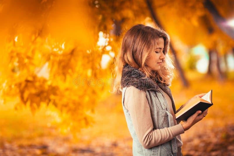 O retrato de uma moça na veste da pele e o livro de leitura no outono do fundo estacionam fotografia de stock royalty free