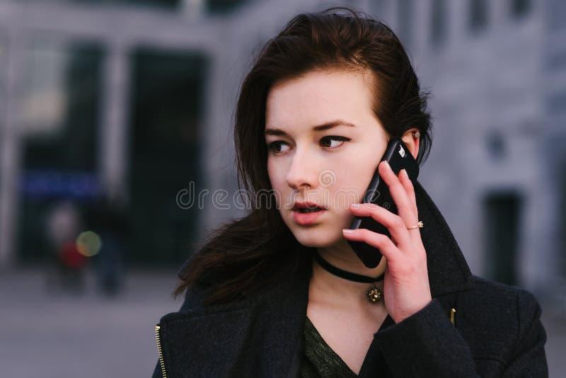 O retrato de uma morena bonita e séria nova da mulher de negócio está falando no telefone em uma cidade um fundo escuro foto de stock