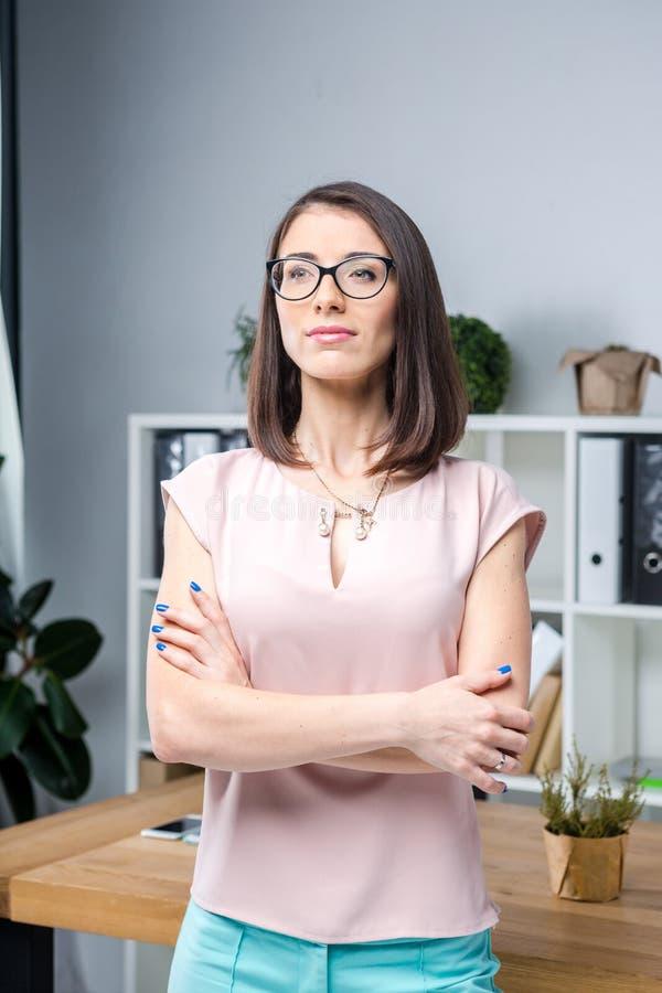 O retrato de uma mulher caucasiano nova bonita de 30 anos nos vidros na blusa cor-de-rosa está estando perto do desktop no escrit foto de stock royalty free