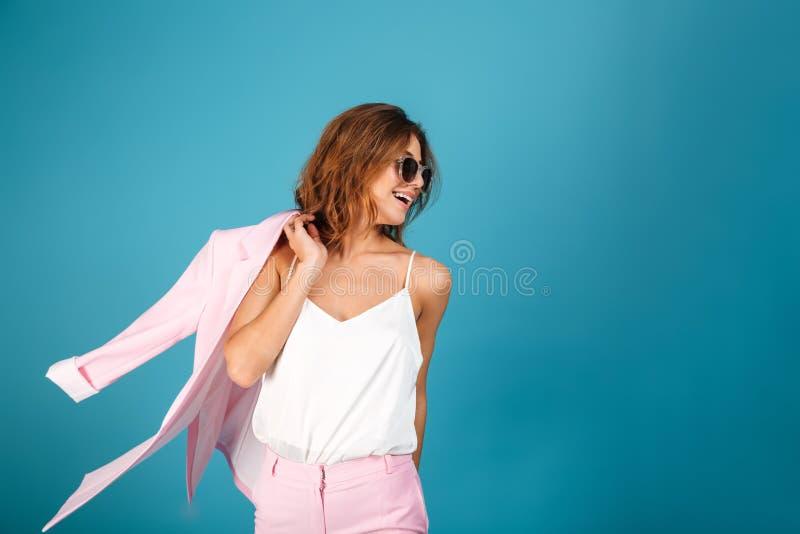 O retrato de uma mulher de sorriso vestiu-se no levantamento cor-de-rosa do terno fotografia de stock royalty free