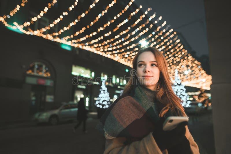 O retrato de uma senhora bonito na roupa morna usa um smartphone, olhares no sentido e sorrisos em uma caminhada de nivelamento imagens de stock royalty free