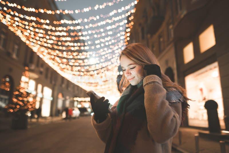 O retrato de uma senhora bonito na roupa morna usa um smartphone, olhares na tela e sorrisos em uma caminhada de nivelamento fotos de stock royalty free