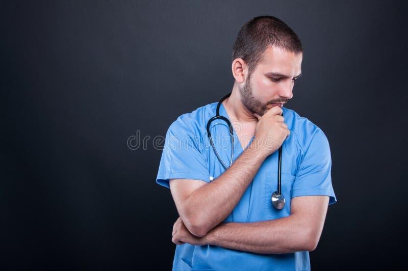 O retrato de vestir do doutor esfrega com pensamento do estetoscópio imagens de stock