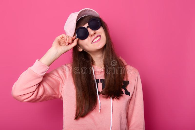 O retrato do adolescente moreno caucasiano de sorriso feliz no hoodie cor-de-rosa curto ? moda, aumentou tamp?o, ?culos de sol pr imagem de stock royalty free