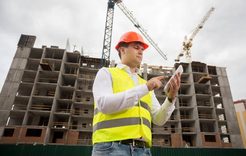 O retrato do arquiteto no capacete de segurança e a segurança investem usando t digital imagens de stock