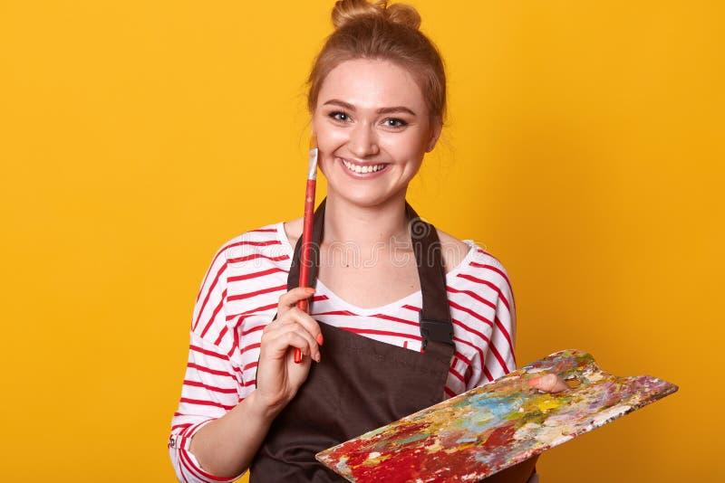 O retrato do artista fêmea talentoso novo faz esboços com óleos brightful, tira no estúdio, tendo o sorriso agradável, pintor fotos de stock royalty free