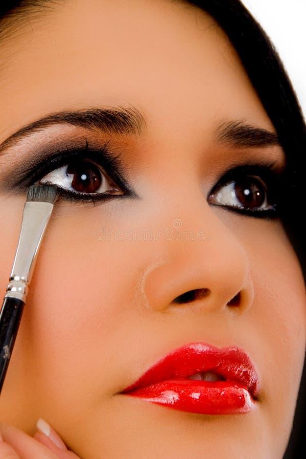 O retrato do beautician que faz o olho compo da mulher fotografia de stock