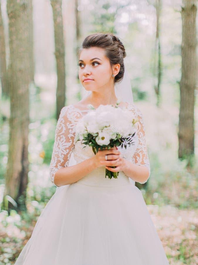 O retrato do busto da noiva séria com o ramalhete do casamento está olhando de lado na floresta fotos de stock royalty free