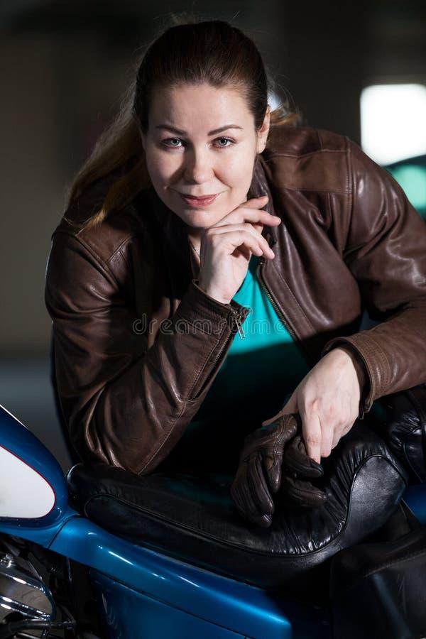 O retrato do cavaleiro fêmea da motocicleta, olhando a câmera, reclina contra a motocicleta na garagem escura fotos de stock royalty free