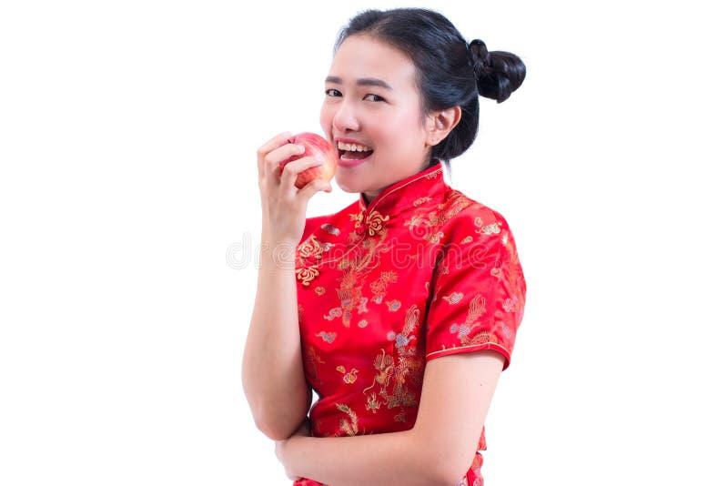 O retrato do chinês asiático novo bonito do desgaste de mulher veste o cheongsam ou o qipao tradicional Comendo a maçã vermelha, fotografia de stock royalty free