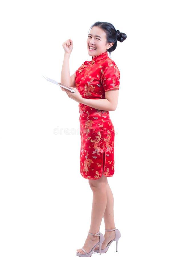 O retrato do chinês asiático novo bonito do desgaste de mulher veste o cheongsam ou o qipao tradicional usando a tabuleta digital imagens de stock royalty free