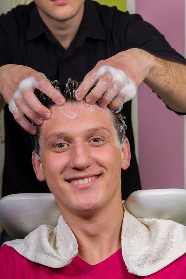 O retrato do cliente masculino que obtém seu cabelo lavou no salão de beleza foto de stock royalty free