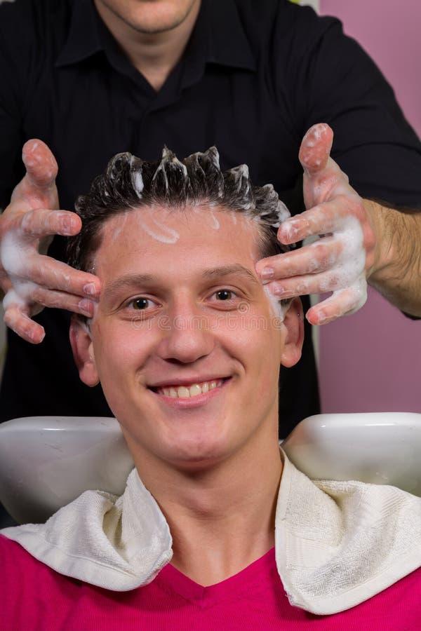 O retrato do cliente masculino que obtém seu cabelo lavou no salão de beleza imagens de stock royalty free