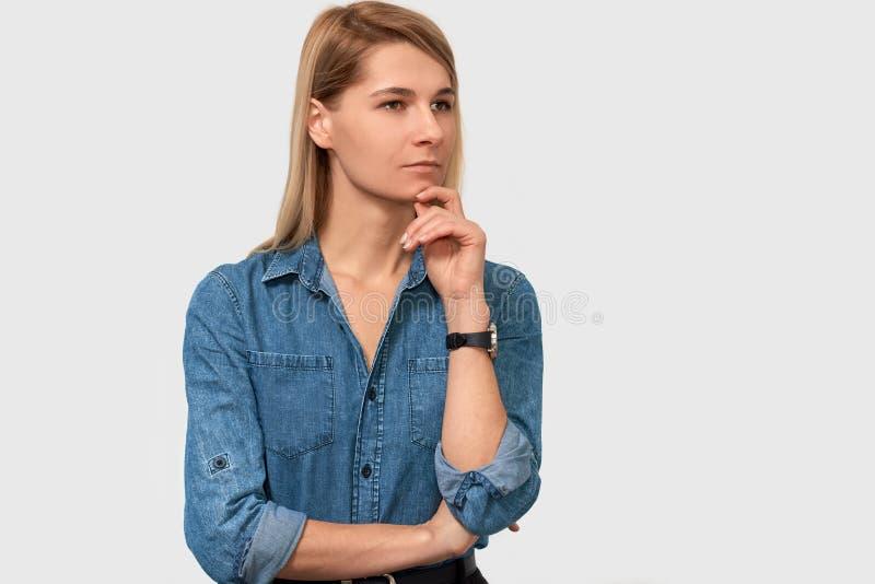 O retrato do close up da jovem mulher bonita pensativa na camisa da sarja de Nimes com dedo dobrou olhar de sobrancelhas franzida fotografia de stock royalty free