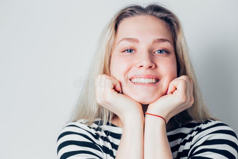 O retrato do close up da mulher beautifulsmiling com pele limpa, natural compõe e os dentes brancos no fundo claro Saúde, juventu fotografia de stock