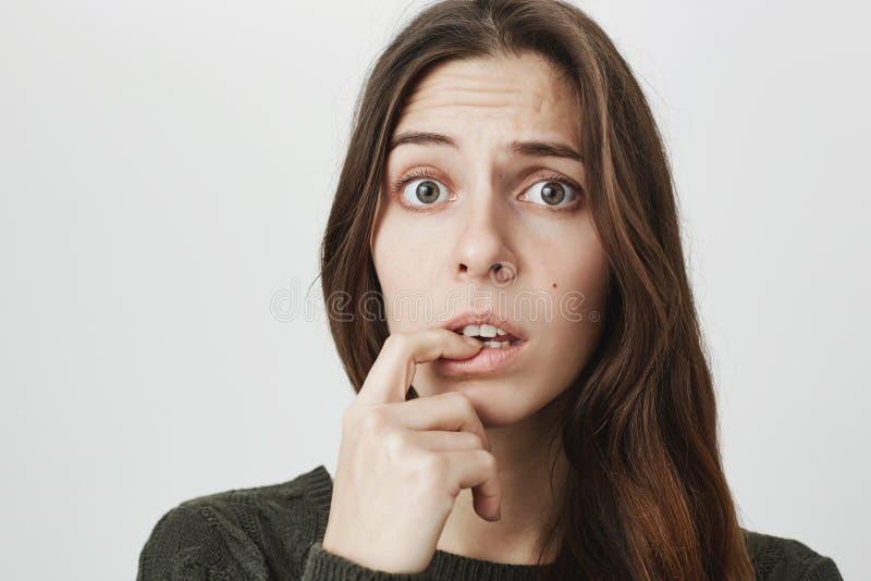 O retrato do close-up da mulher confusa confundida com cabelo longo escuro vestiu-se ocasionalmente, olhando a câmera com perplex imagens de stock