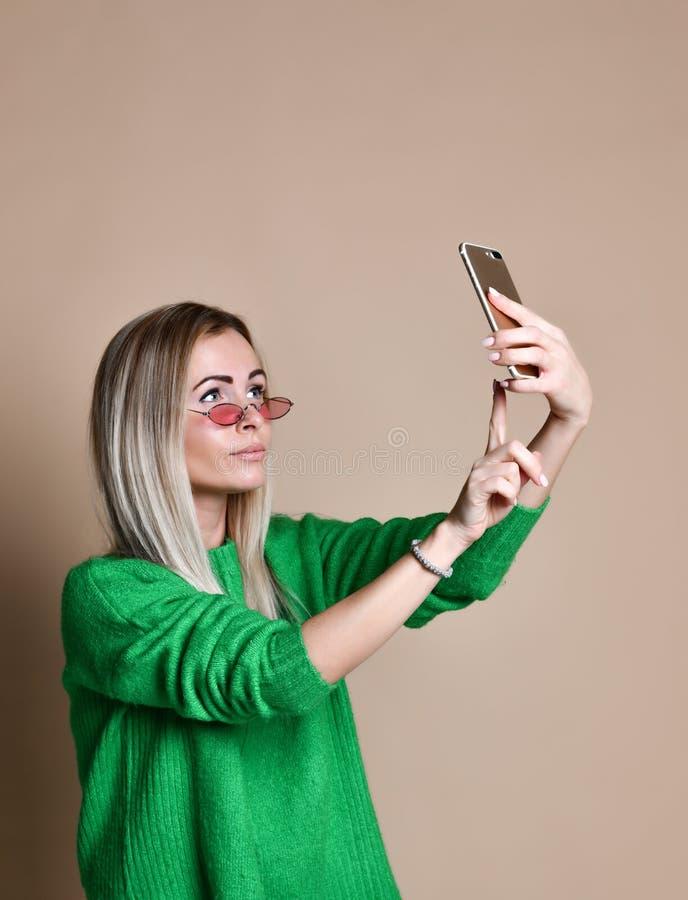 O retrato do close-up da mulher loura da forma alegre nova no desgaste da camiseta faz o selfie no smartphone, sobre o fundo bege imagens de stock royalty free