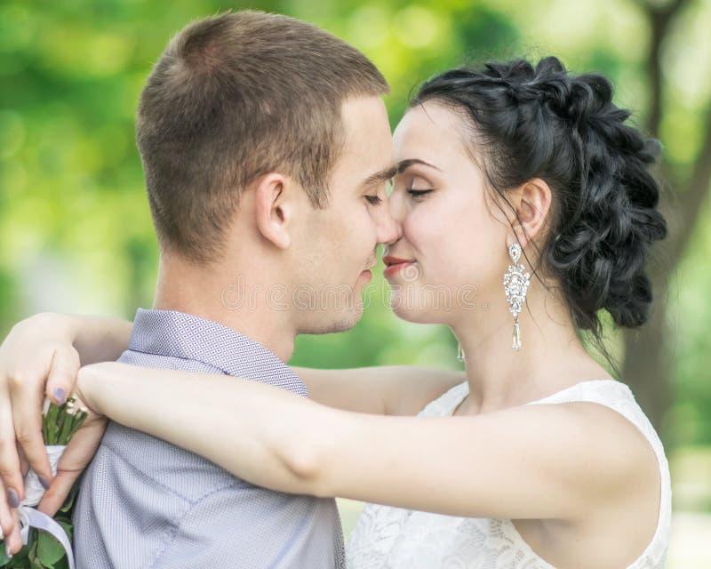 O retrato do close-up da noiva fêmea dos pares novos bonitos e o noivo do homem que beija no verão estacionam Esposa da mulher qu fotografia de stock