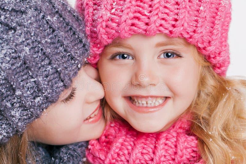 O retrato do close-up de duas irmãs mais nova bonitos no inverno veste-se Chapéus e lenços cor-de-rosa e cinzentos Família imagem de stock royalty free