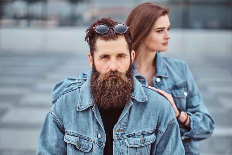 O retrato do close-up de um par do moderno de um homem farpado brutal e de sua amiga vestiu-se em revestimentos das calças de bri fotografia de stock
