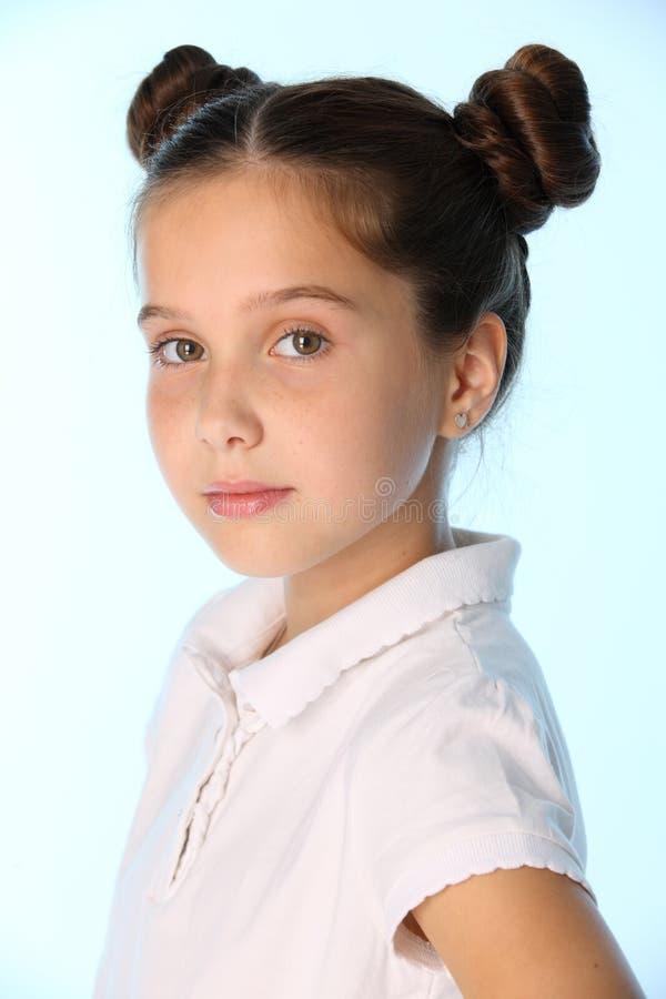 O retrato do close-up de uma menina moreno consideravelmente à moda da criança olha seriamente e atentamente imagem de stock