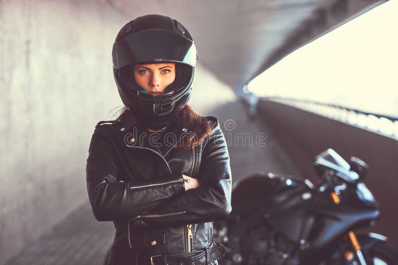 O retrato do close-up de uma menina do motociclista com seus braços cruzou-se ao lado de seu superbike dentro da ponte fotos de stock royalty free