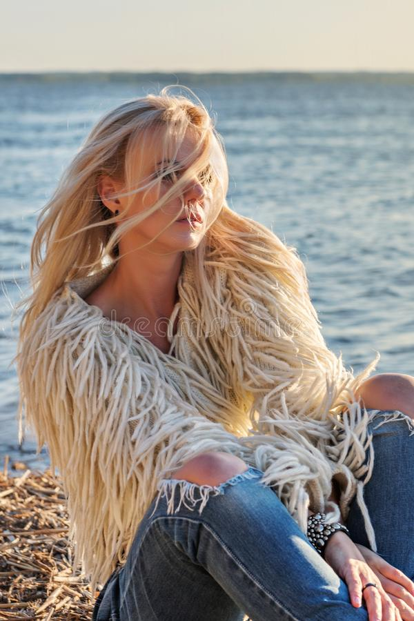 O retrato do close-up de uma mulher loura atrativa nova com cabelo dispersou o voo do vento nos raios de um sol brilhante imagens de stock