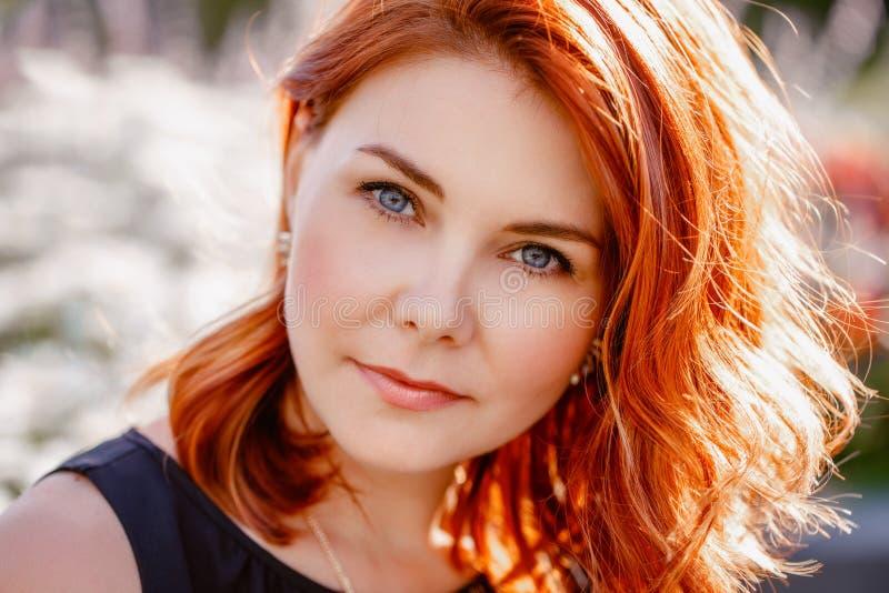 O retrato do close up do meio envelheceu a mulher caucasiano branca com cabelo vermelho encaracolado acenado com olhos azuis foto de stock royalty free